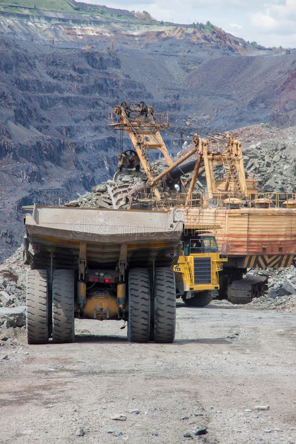 Mining. Heavy mining trucks being loaded with iron ore stock photo