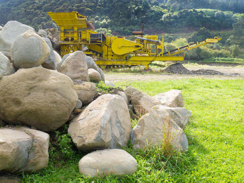 Mining industry rock crusher in stone quarry pit. Large boulders and heavy-duty yellow rock crusher machinery used to crush rock in a stone quarry pit or mining stock images