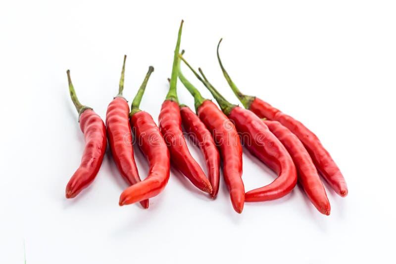Minipeulen van het rode hete additief van de Spaanse peperpeper aan vlees en kip die aroma geven aan een groep groenten op een wi stock foto