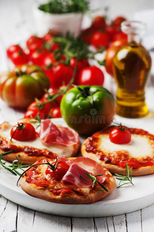 Minipizza mit Mozzarella, Prosciutto und Tomate stockbilder