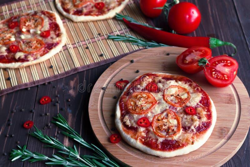 Minipizza mit Tomaten auf einem dunklen Hintergrund stockbild