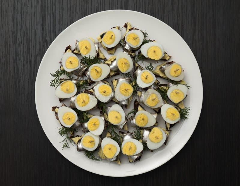 Minisandwich met zoute sprot en gesneden gekookt kwartelsei op de boterham De ingeblikte vis is Estlands nationaal voedsel Concep stock afbeeldingen