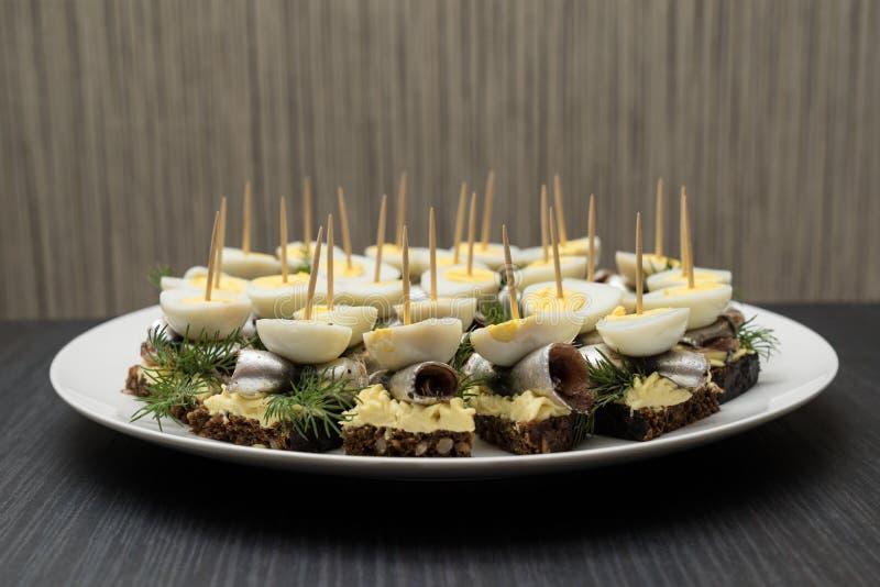 Minisandwich met zoute sprot en gesneden gekookt kwartelsei op de boterham De ingeblikte vis is Estlands nationaal voedsel Concep stock afbeelding