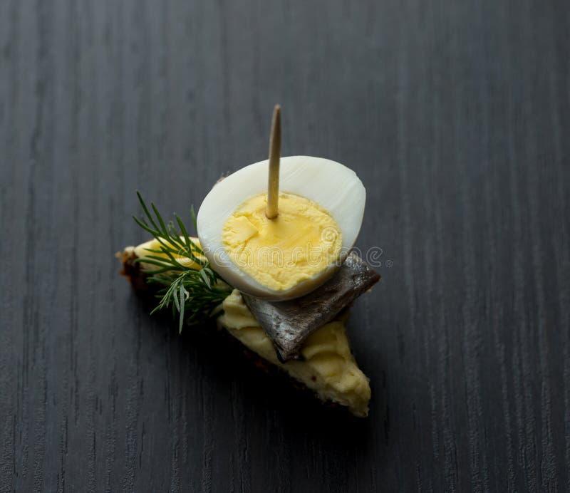 Minisandwich met zoute sprot en gesneden gekookt kwartelsei op de boterham De ingeblikte vis is Estlands nationaal voedsel Concep stock fotografie