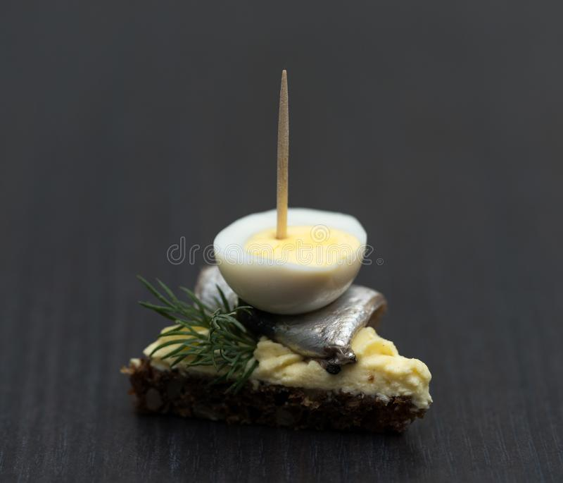 Minisandwich met zoute sprot en gesneden gekookt kwartelsei op de boterham De ingeblikte vis is Estlands nationaal voedsel Concep royalty-vrije stock fotografie