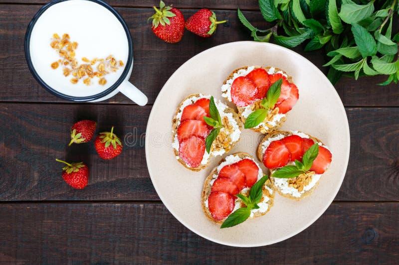 Minisandwiches met kwark, verse die aardbeien, met muntbladeren worden verfraaid op roggebrood en een mok yoghurt stock fotografie