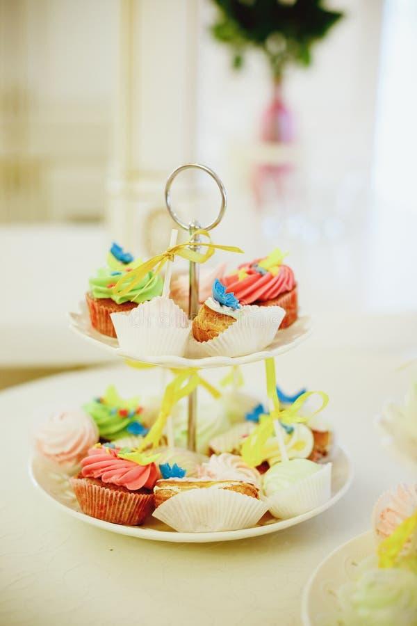 Minischokoladenkleine kuchen überstiegen mit mini rosa Schaumgummiringen auf einer Nachtischtabelle Sie werden auf einem abgestuf lizenzfreie stockbilder