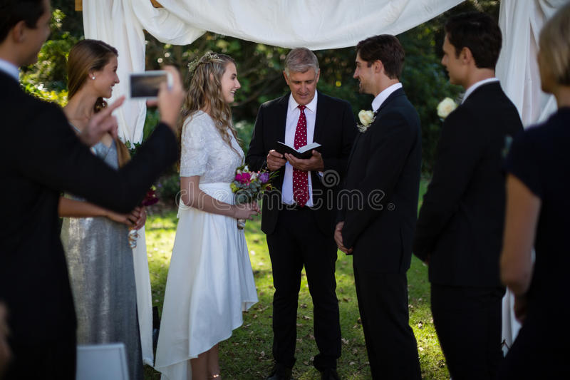 Minister giving speech to bride and groom stock photography