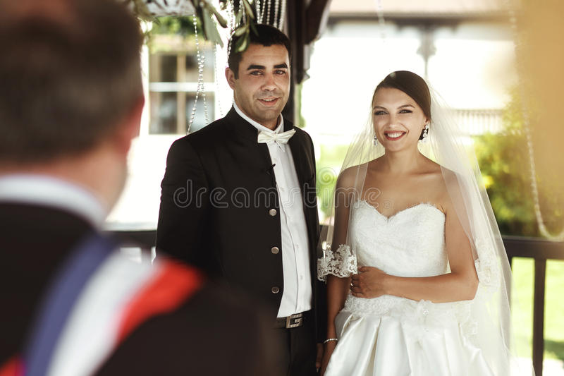 Minister providing wedding ceremony for married couple under arbor royalty free stock photo