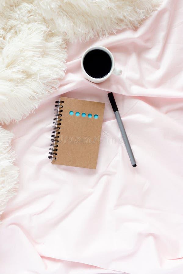 Ministerio del Interior en cama con la taza de café, libreta de Kraft, pluma en los linos rosados foto de archivo libre de regalías