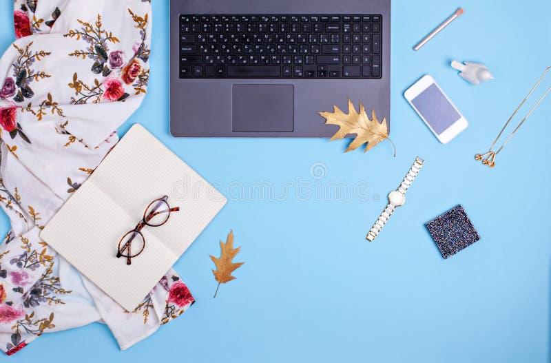 Ministerstwo Spraw Wewnętrznych workspace z laptopem, szkłami i suknią na błękitnym tle, Mody blogger pracy pojęcie zdjęcia royalty free