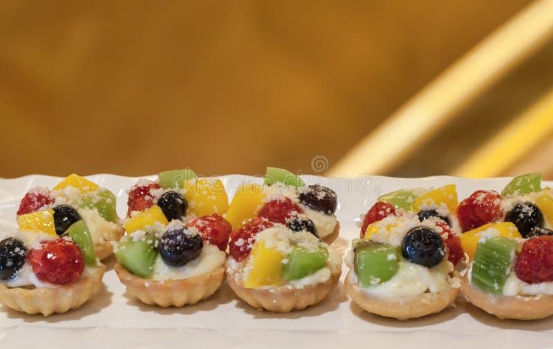 Minitaartjes met room en bessen Heerlijke minitaartjes met verse bessen en vla op lijst stock foto's