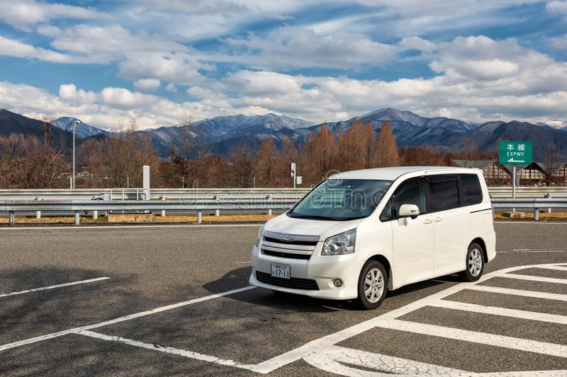 Minivan at expressway rest area, Yamanouchi. Yamanouchi, Nagano, Japan - April 12, 2019: Minivan parking at expressway rest area with central apls mountain royalty free stock photography