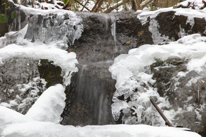 Miniwasserfall bedeckt mit Eis und Schnee lizenzfreie stockfotos