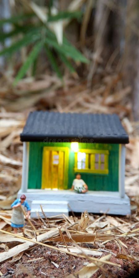 Minizahl die indonesische Frau des Spielzeugs, welche die Terrasse und den alten Mann unter Verwendung des sarung säubern, kopiah stockbilder