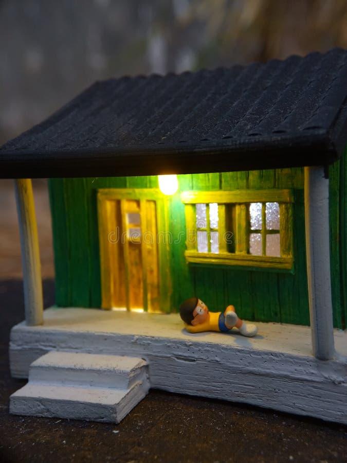 Minizahl die indonesische Frau des Spielzeugs, welche die Terrasse und den alten Mann unter Verwendung des sarung säubern, kopiah stockfotos