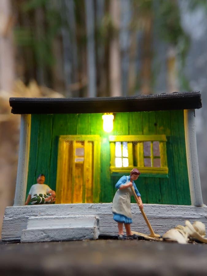 Minizahl die indonesische Frau des Spielzeugs, welche die Terrasse und den alten Mann unter Verwendung des sarung säubern, kopiah lizenzfreie stockfotografie