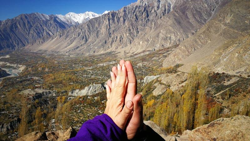 Minnaarhanden die en met berg en blauwe hemelachtergrond raken togethering voor liefde en helend concept stock afbeelding