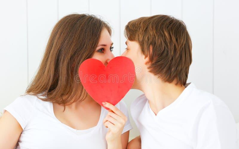 Minnaarpaar het kussen met een rood hart in bed royalty-vrije stock foto's