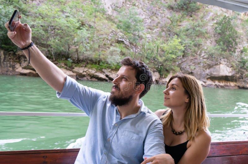 Minnaars die een selfie met een celtelefoon nemen die van een weekend geniet dat samen, in een boot zit die een reis in een rivie royalty-vrije stock afbeeldingen
