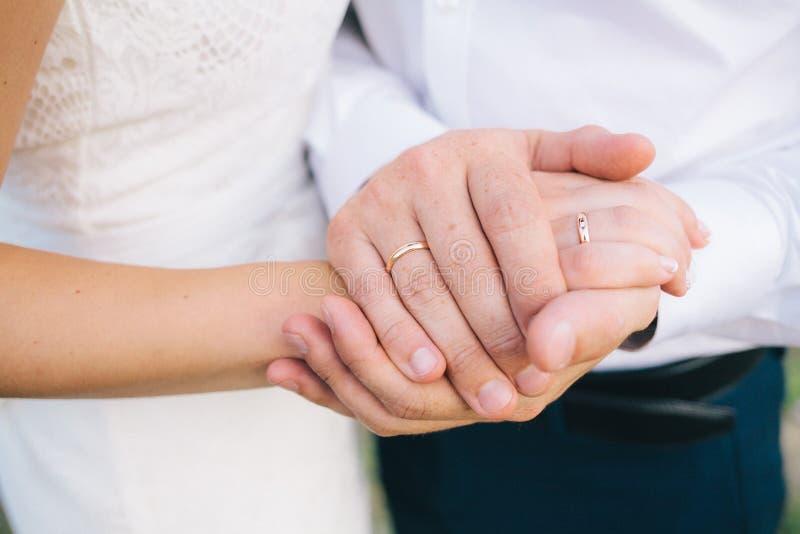 Minnaars die handen met gouden trouwringen houden royalty-vrije stock fotografie