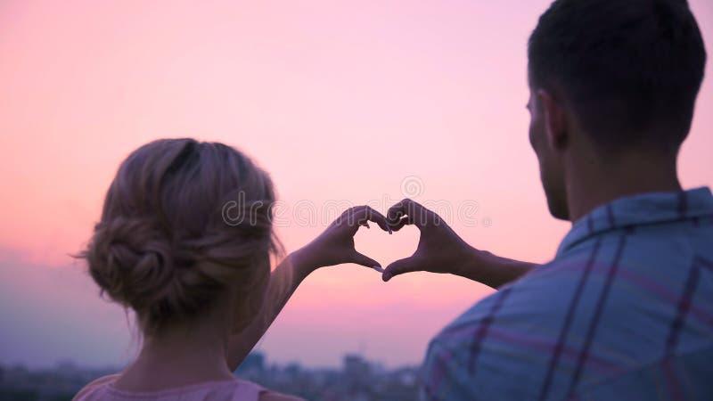 Minnaars die hun handen in vorm die van hart samenbrengen, hun liefde aantonen stock fotografie