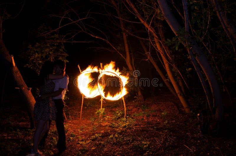 Minnaarsjongen en meisje op de achtergrond van twee ringen van brand royalty-vrije stock foto's