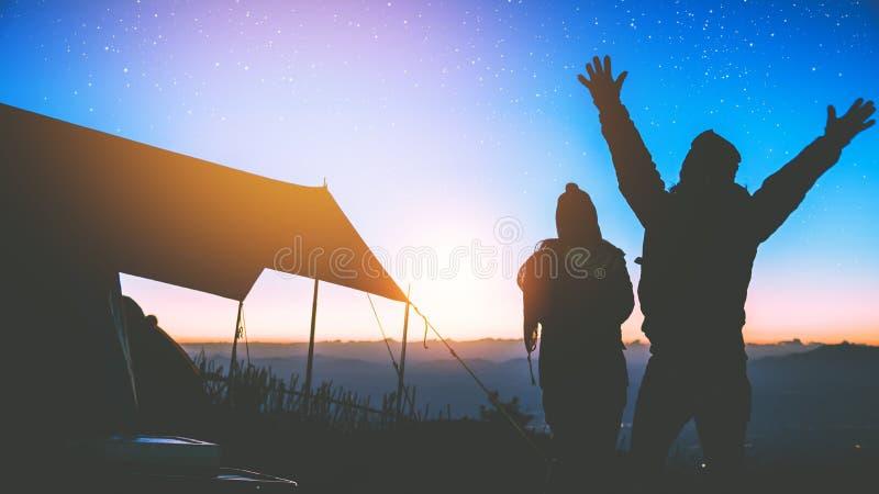 Minnaarvrouwen en mannen Aziatische reisaard De reis ontspant E Het kamperen op de berg let op de zonstijging In royalty-vrije stock afbeeldingen