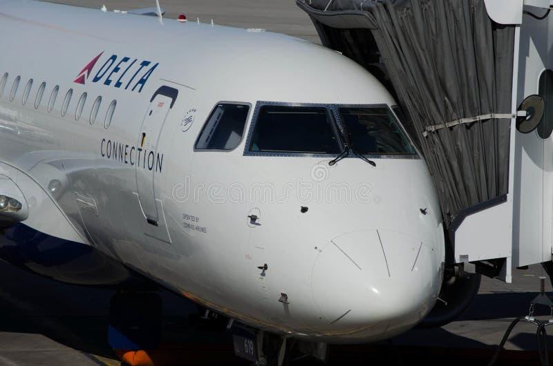 Minneapolis, manganês - um avião do jato da conexão de delta de Delta Air Lines espera em uma porta no aeroporto internacional de foto de stock