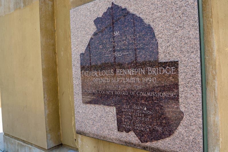 Minneapolis, Minnesota - 2 de junho de 2019: Chapa que dá a informação histórica sobre o pai Louis Hennepin Bridge, construído de imagens de stock royalty free