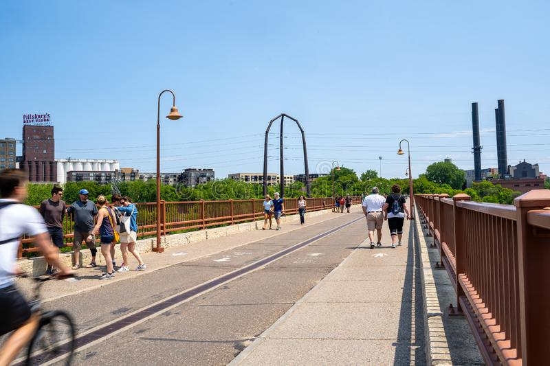 Minneapolis, Minnesota - June 1, 2019: Pedestrians and bikers enjoy a beautiful spring day walking over the Stone Arch Bridge in stock photos