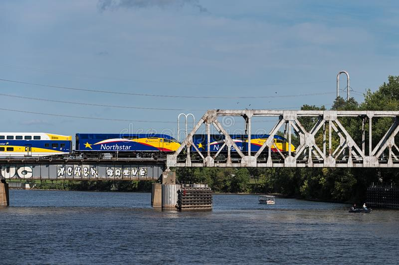 """MINNEAPOLIS, MN †""""WRZESIEŃ 9, 2018: Northstar kolejka rusza się wschód przez most nad rzeką mississippi Northstar zdjęcie royalty free"""