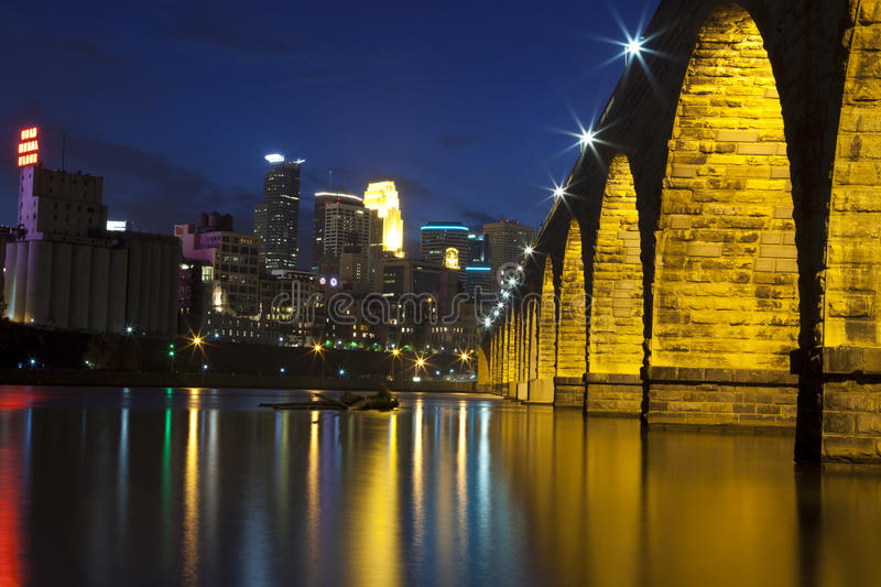 Minneapolis at night. Minneapolis skyline at night reflected in the Mississippi river with the famous Stone Arch Bridge royalty free stock photography