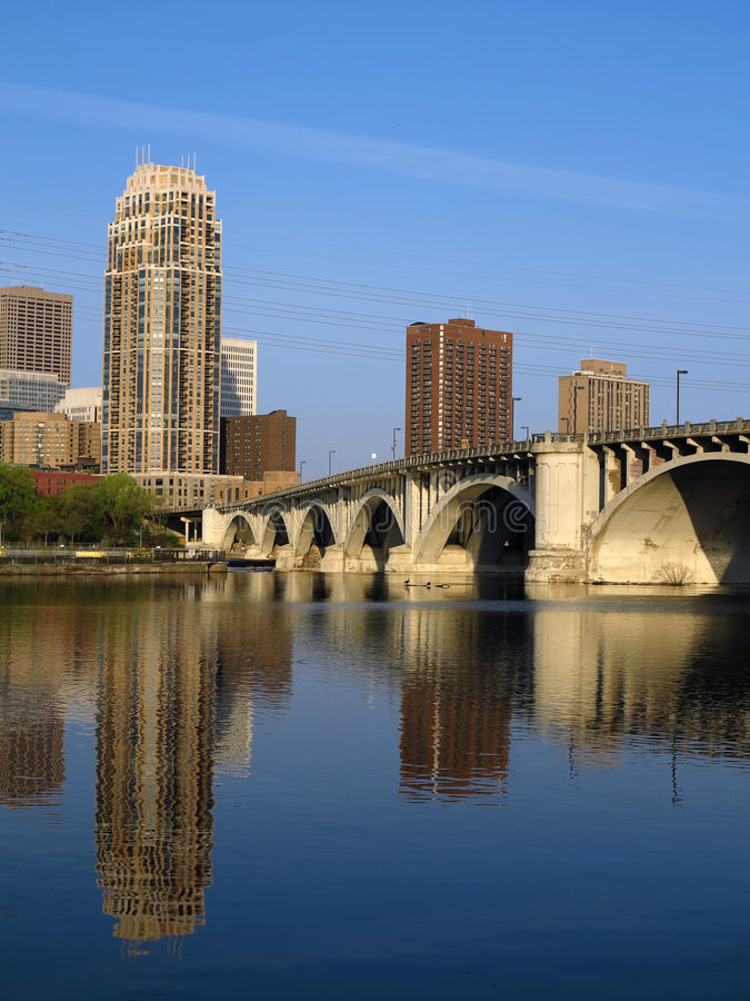 Minneapolis Urban City 3. Minneapolis downtown with its many modern towers and the Central Avenue bridge, over the Mississippi River. Photo taken at dawn from stock photo