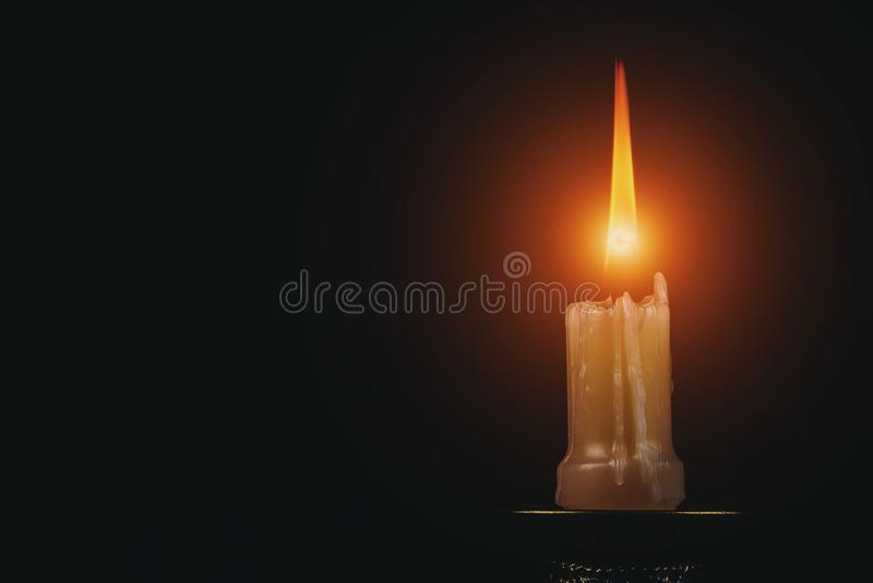 Minnes- skott av en stearinljusflamma på svart bakgrund arkivfoto