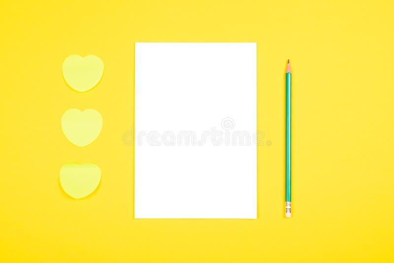Minneslistaklistermärkear och anteckningsbok på gul bakgrund royaltyfria foton