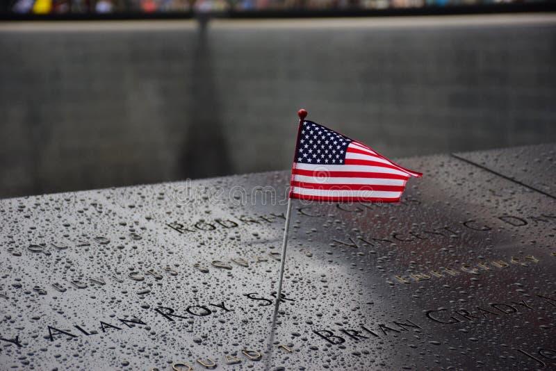 Minnesmärke på ground zero Manhattan för den September 11 terroristen Attack med ett amerikanska flaggananseende nära namnen av o royaltyfria foton