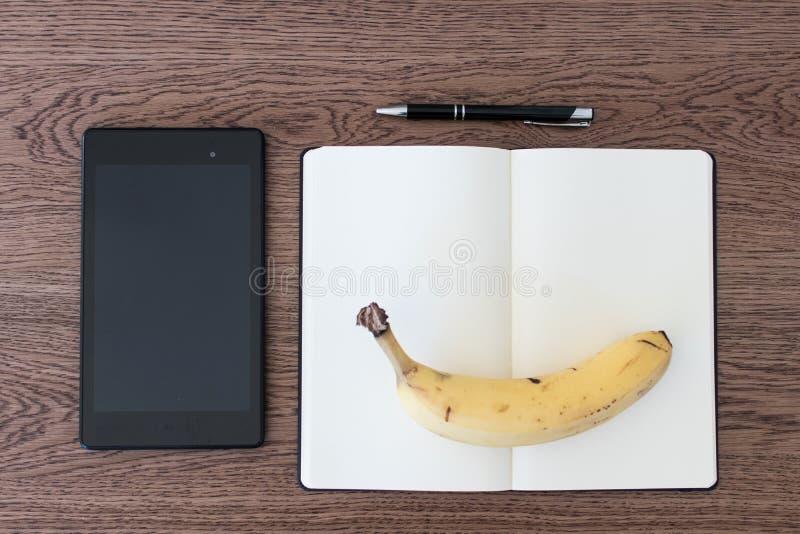 Minnestavla, anteckningsbok, penna och en banan på en trätabell Conc bild royaltyfri foto
