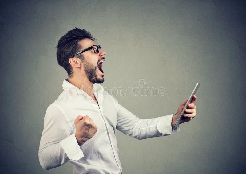 Minnestavla och näve för gladlynt hipsterman hållande upp, medan skrika med lycka arkivfoto