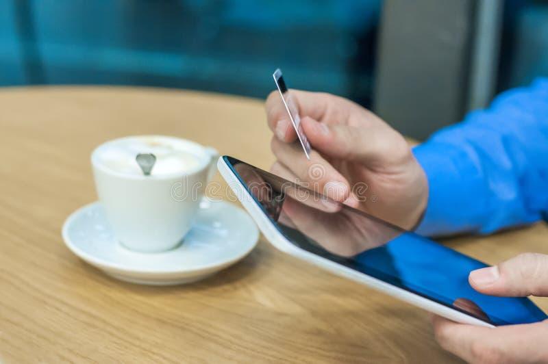 Minnestavladator i manhänder Man den hållande den inomhus minnestavlaPC:n och kreditkorten, online-shopping fotografering för bildbyråer