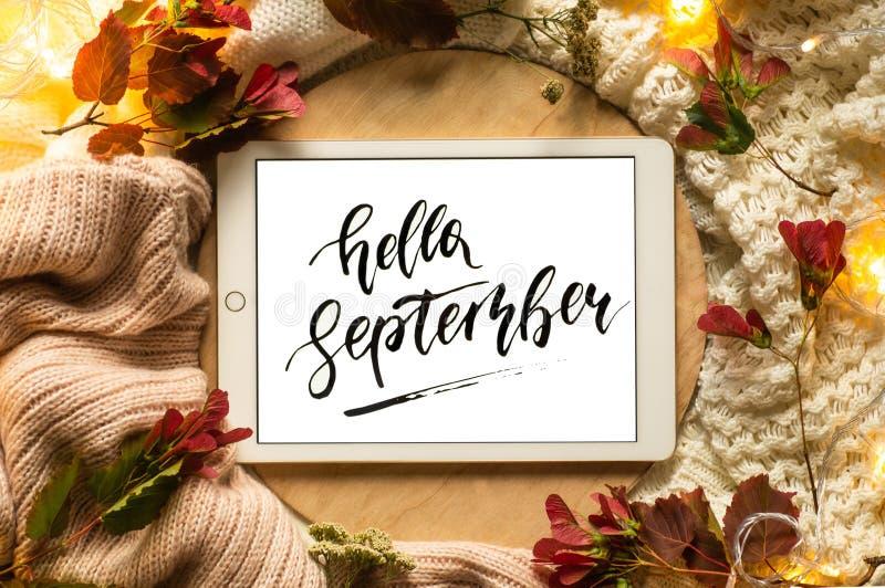 Minnestavlan säger ordhälsningarna September med röda sidor och ett podium på träbakgrunden Begrepp av hösten royaltyfri foto
