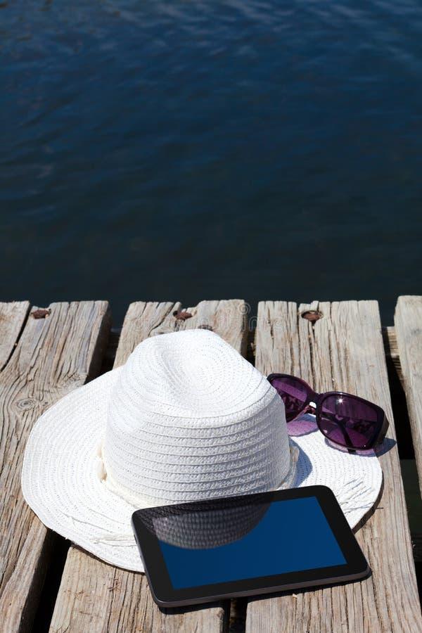 MinnestavlaPC och sugrörhatt på simningsjön royaltyfria foton