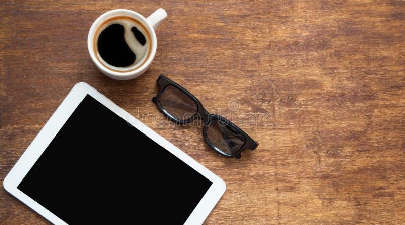 MinnestavlaPC som ser som ipad på den wood tabellen med kaffe- och svartexponeringsglas, lekmanna- lägenhet arkivbilder