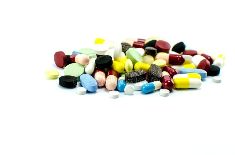 Minnestavlor och kapslar med medicin av olika färger och format på en vit bakgrund arkivbilder