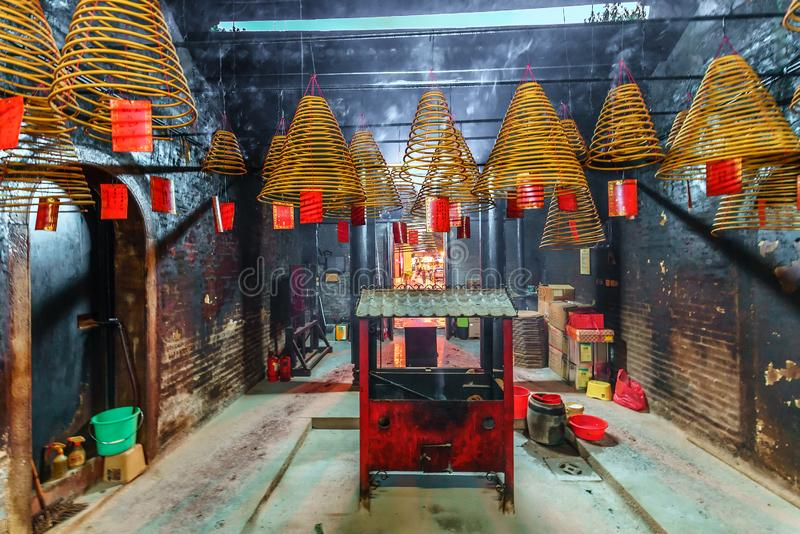 Minor Buddhist temple interior in Macau. Incense prayer cones and censer in which they are burnt royalty free stock photo