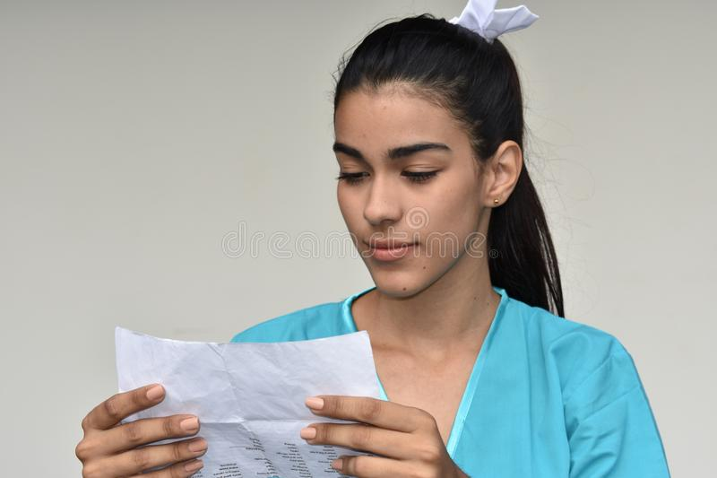 Minority Female Nurse Reading Papers. A pretty young Colombian teen girl royalty free stock images