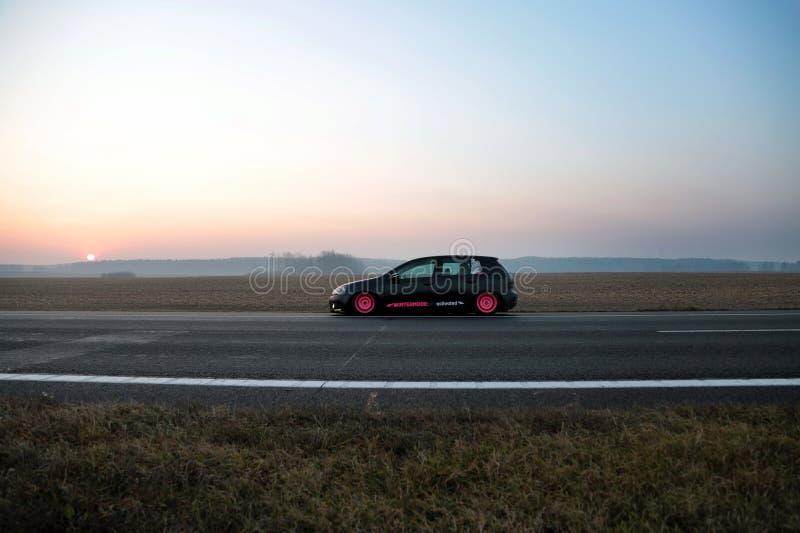minsk Зима 2018 Черный гольф Volkswagen настроенный с розовыми оправами на дороге между городами На фоне стоковое фото rf