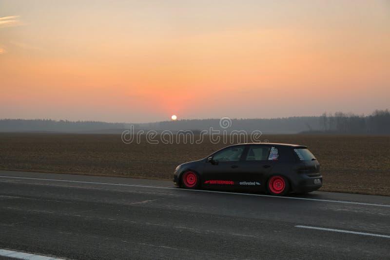 minsk Зима 2018 Черный гольф Volkswagen настроенный с розовыми оправами на дороге между городами На фоне стоковые изображения rf