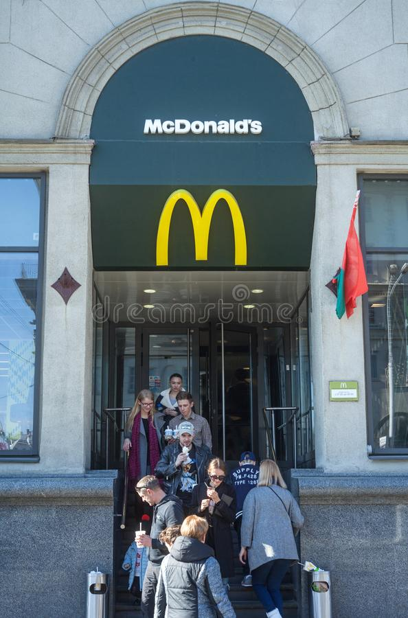 Minsk, Belarus, April 4, 2018: Visitors enter and exit from the McDonald`s restaurant. royalty free stock photo