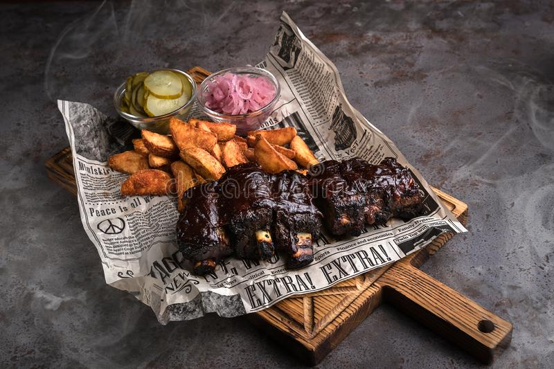 Minsk, Belarus - August, 2019 BBQ Pork ribs set with baked potato and pickled cucumber serve with newspaper on wooden background. Board that lie on a gray stock photo